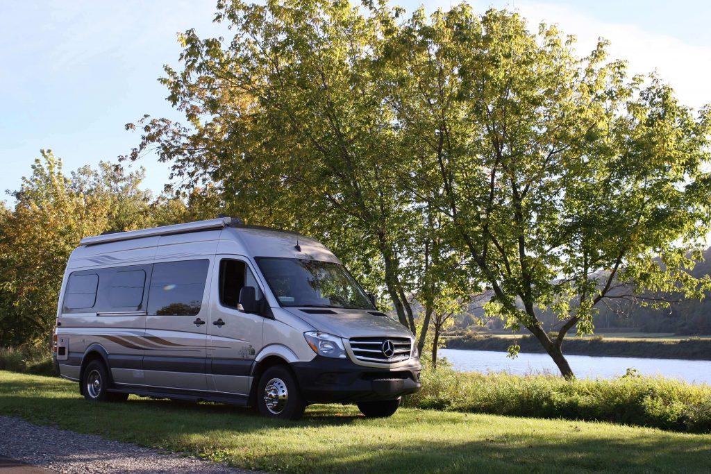 Le van Condo Safari Sprinter XL Plus garé au bord d'une rivière