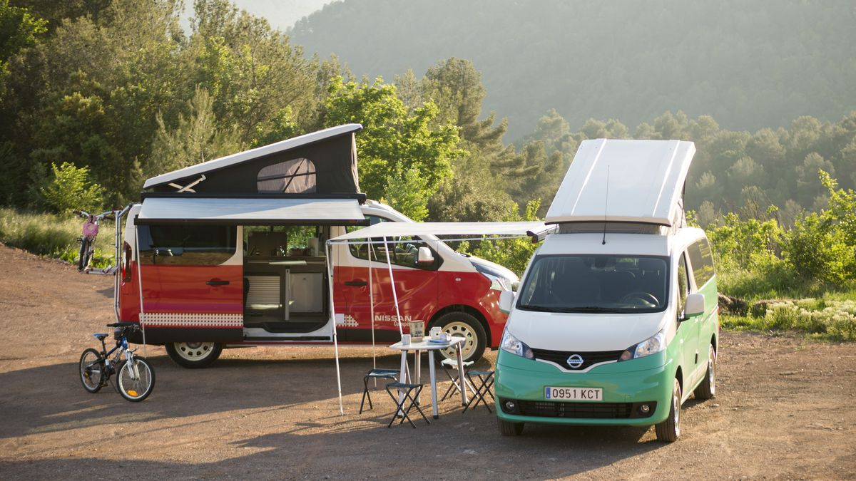 Deux camping-cars garés l'un à côté de l'autre. Une camionnette est verte et blanche. L'autre fourgon est rouge et blanc. Les deux fourgons ont des toits extensibles gonflables. Il y a un vélo, une table et des chaises à côté des fourgons.