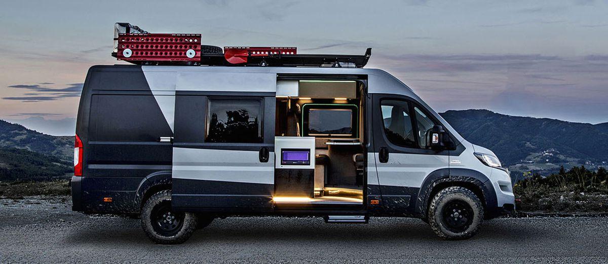 Un camping-car gris et noir. Les portes sont ouvertes et l'intérieur a des sièges et une chaîne stéréo. Il y a des compartiments de rangement rouges sur le toit de la camionnette.