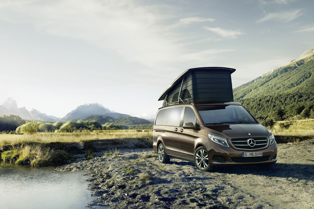 Une camionnette marron, la Mercedes Marco Polo. Il a une tente gonflable sur le toit. La camionnette est garée dans un champ. Il y a des montagnes au loin.
