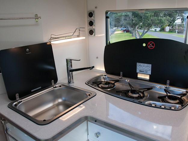 La cuisine du camping car Rapido 8094dF est petite mais fonctionnelle avec un évier inox et une plaque 3 feux