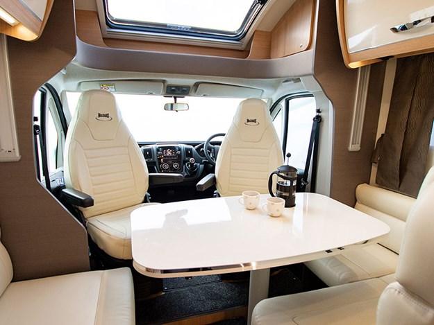 Camping car McLouis Fusion vu intérieure du joli salon avec les sièges et la table blancs