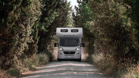 Camping car avec capucine sur la route vu de face