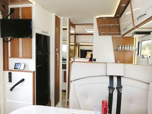 Vue intérieure du camping-car Pilote Emotion G781C  à partir du salon avec la télé en haut à gauche sur la paroi