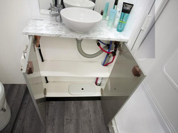 Le lavabo et les grands placards portes ouvertes en dessous