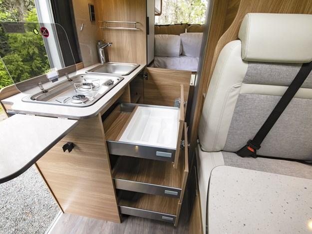 La cuisine du van Carado Vlow 600 est petite mais fonctionnelle. On voit la plaque 3 gaz, l'évier et 3 tiroirs ouverts
