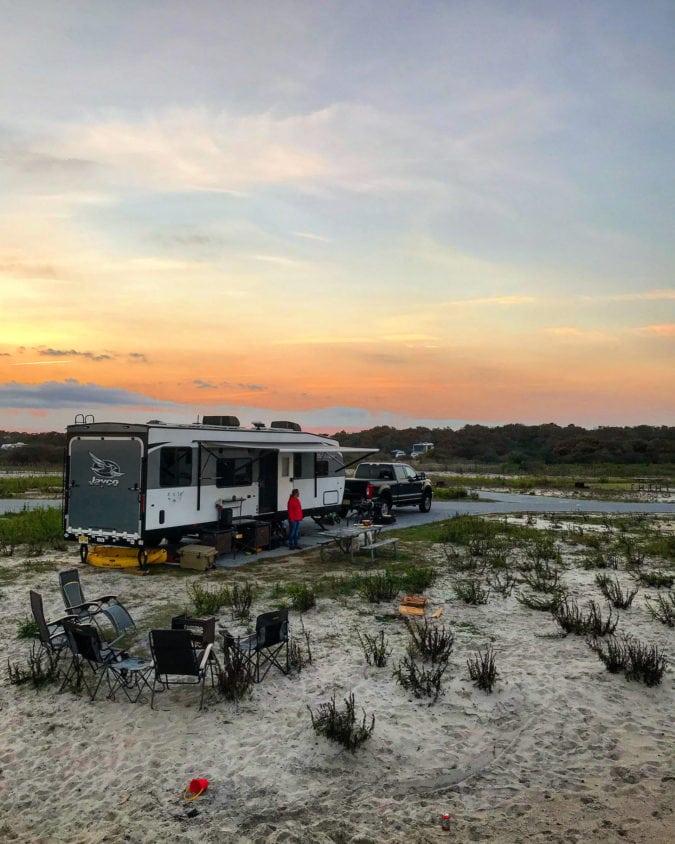 Un coucher de soleil sur un camping-car dans un camping sablonneux