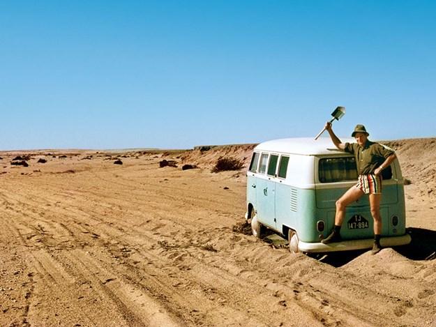 Un VW combi classique dans le sable un homme debout sur le pare choc arrière avec une pelle us
