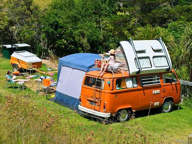 Un VW combi classique orange complètement restauré avec tente sur le toit