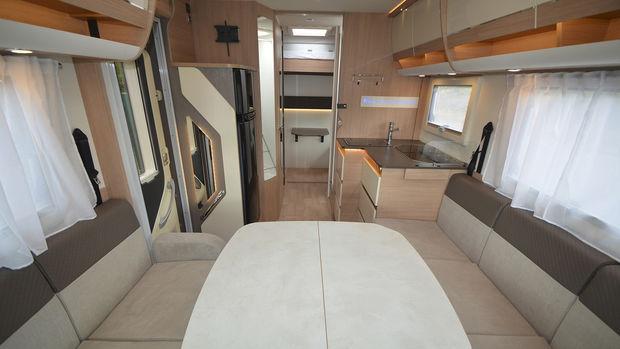 Vue intérieure du camping-car Itineo SC 700 avec sa table centrale les 2 banquettes et le coin cuisine à droite
