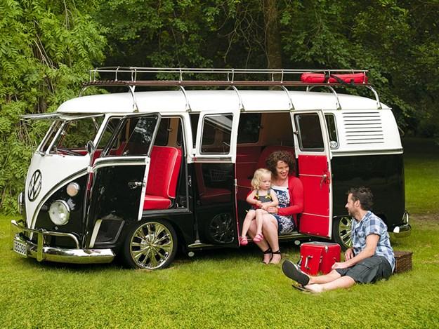 VW combi classique et son histoire : garé sur l'herbe portes ouverte un couple et son bébé
